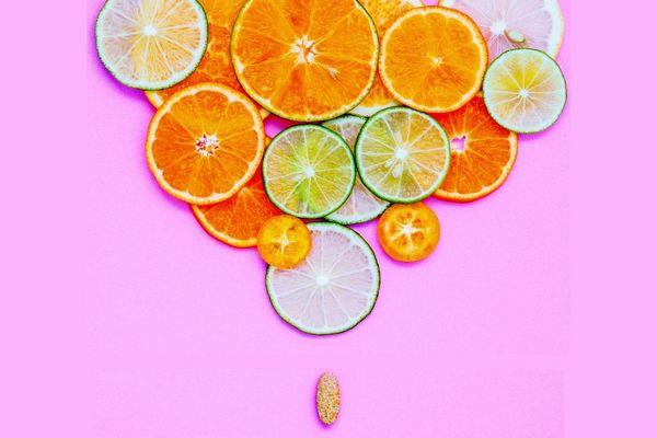 Egy rózsaszínű háttér előtt narancszeletek, citromszeletek és limeszeletek, melyek alatt egy vitamintabletta található.