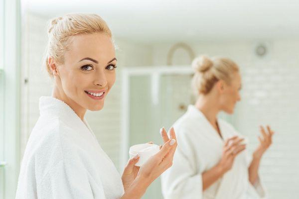 Egy fürdőszobában fiatal nő ekcémára való arckrémes tégelyt tart a kezében.