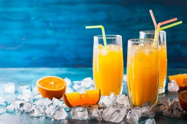 Egy asztalon jégkockák között három üvegpohárban házilag készített narancsos elixír megfázásra és köhögésre.