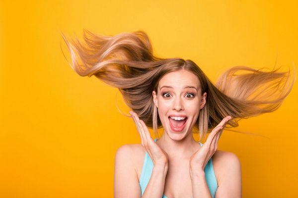 Egy sárga háttér előtt egy vörös hajú fiatal lány csodálkozóan nevet, kezeit arcához emeli.