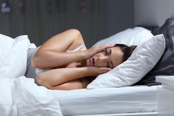 Fiatal nő az ágyában fekszik, két kezével elfáradt arcát fogja, mert nem tud aludni.