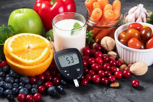 Egy asztalon vércukorszintmérő és rostgazdag gyümölcsök és zöldségek, narancs, fekete áfonya, vörös áfonya, alma, paprika, sárgarépa, fokhagyma, paradicsom, dió, mandula.