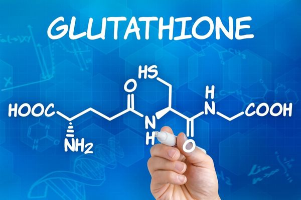 Egy kék háttér előtt a glutathione felirat és a glutation kémiai összetételét mutató ábra, melyre egy kéz fehér tollal rámutat.