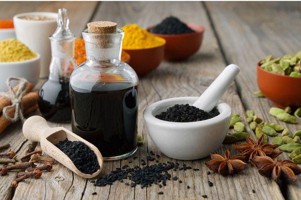 Egy asztalon feketeköménymag-olaj üvegekben, mellettük feketeköménymagok egy tálban és fakanálban, illetve csillagánizs, kardamom, fahéjrudak.