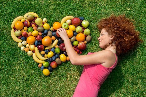 Egy zöld füvön egy fiatal vörös hajú lát fekszik, mellette szív alakban gyümölcsök elhelyezve.