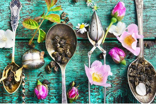 Egy türkizzöld asztalon kanalakban és mellettük többféle szálas tea és virágok.