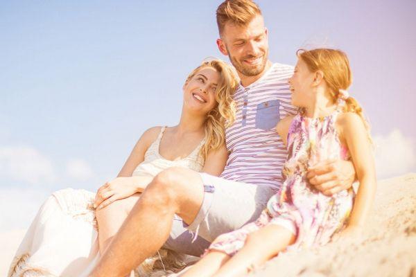 Egy egy család ül a természetben, anya, apa és a kislányuk egymásra nézve mosolyognak.
