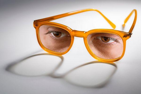 Egy szürke háttér előtt sárga szemüvegkeret, mögötte egy szempár.