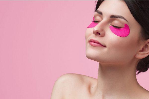 Egy rózsaszínű háttér előtt fiatal nő csukott szemmel magenta színű szem alatti maszkban pihen.