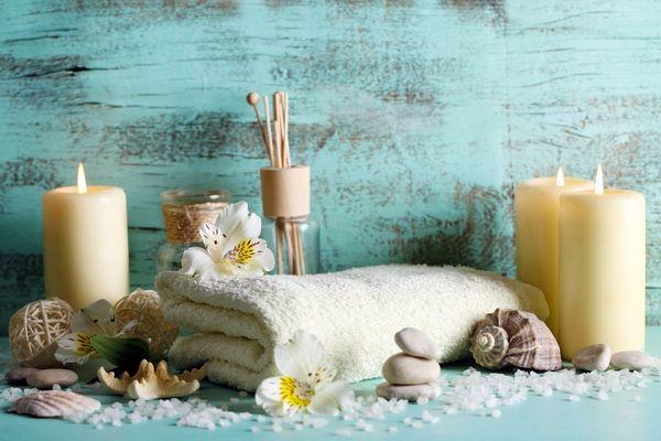 Egy türkizkék háttér előtt gyertyák, fehér törölköző, illatosító, fürdősó, kagylók.