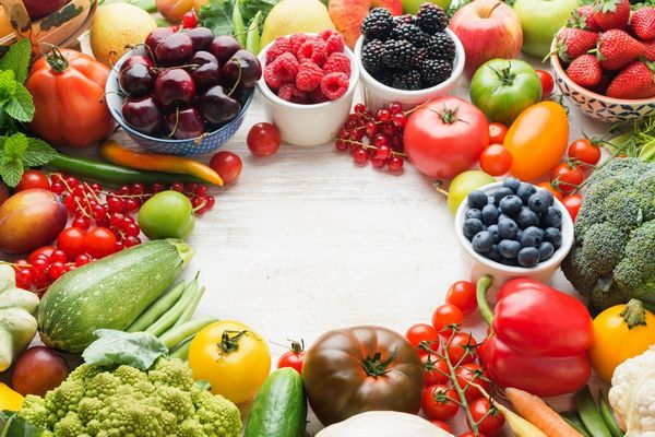 Egy asztalon rostban gazdag zöldségek és gyümölcsök, paradicsom, uborka, paprika, brokkoli, szeder, málna, fekete áfonya, piros ribizli, alma.
