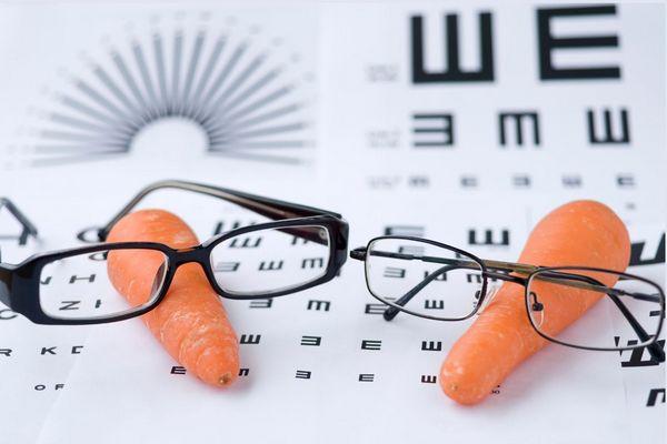 Egy szemvizsgáló lapon két sárgarépa, melyeken fekete keretes szemüvegek.