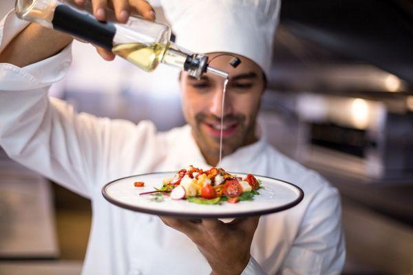 Egy olasz konyhában egy fehér ruhás szakács magasra emel egy tányért, melyen egészséges olasz étel, saláta van, jobb kezével olíva olajat csöpögtet rá.