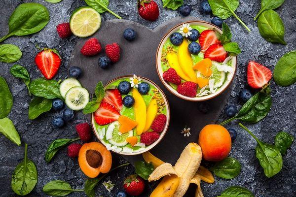 Egy sötét színű háttér előtt sok gyümölcs és zöldség, tálakban és mellettük, spenótlevelek, fekete áfonya, banán, kajszi barack, málna, eper. lime.