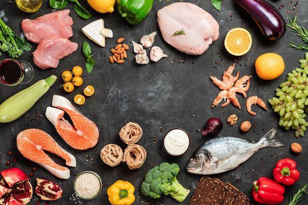 Egy szürke asztalon sok egészséges élelmiszer, lazac, hal, brokkoli, tengeri rák, paprika, gránátalma, szőlő, citrom, padlizsán, hagyma, dió, cukkini, mandula, spenót, fokhagyma, sajt, vörös bor, csirkehús..