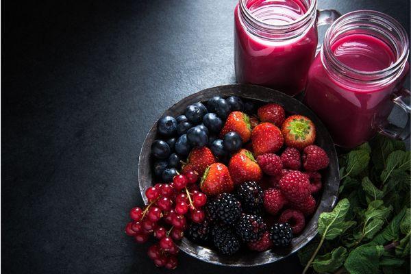 Egy sötét szürke asztalon egy tálban antioxidánsokban gazdag bogyós gyümölcsök, fekete áfonya, piros ribizli, eper, málna, szeder, mellettük üvegekben gyümölcslé és spenótlevelek.