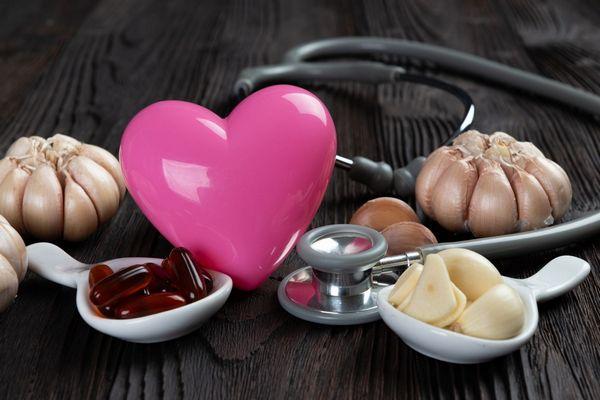 Egy szürke asztalon rózsaszínű műanyag szív és fonendoszkóp, mellettük kis tálban fokhagymagerezdek és fokhagymakapszulák és fokhagymák.