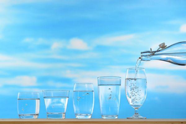 Egy kék háttér előtt öt üvegpohár tele vízzel, az ötödikbe vizet öntenek egy üvegből.