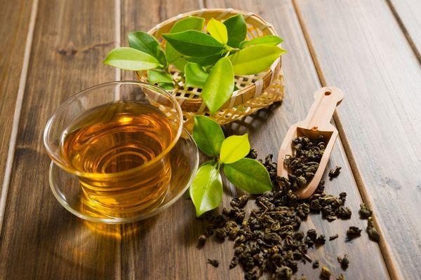 Egy asztalon egy üveg teáscsészében fekete tea, mellette tealevelek és egy fakanálban szálas fekete tea.
