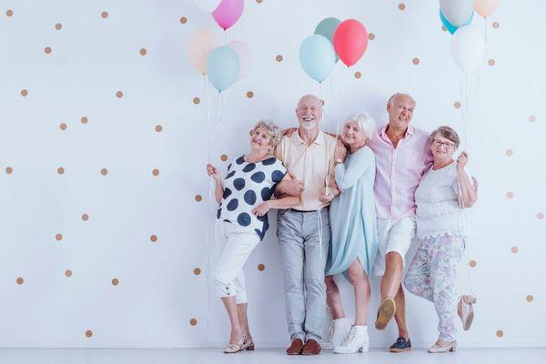 Egy pöttyös háttér előtt egymásba kapaszkodva mosolygós nyugdíjas korú férfiak és nők állnak, kezükben színes lufik.