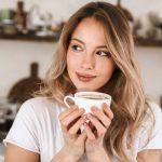 Fiatal mosolygós nő egy kávézóban két kezével kávéscsészét tart, miközben oldalra néz.