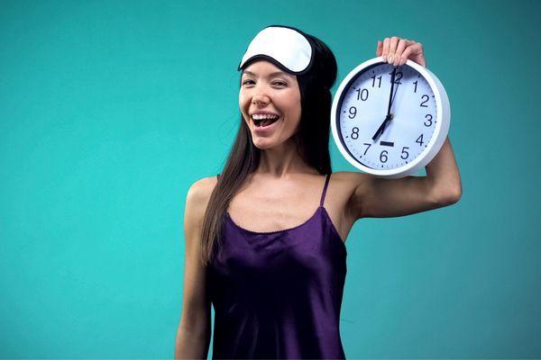 Egy zöld háttér előtt egy lila kombinés lány, kezében egy nagy óra.