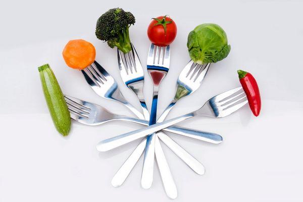 Hat villa, melyekre különféle zöldségek vannak felszúrva, cukkini, sárgarépa, brokkoli, paradicsom, kelbimbó és chilipaprika.