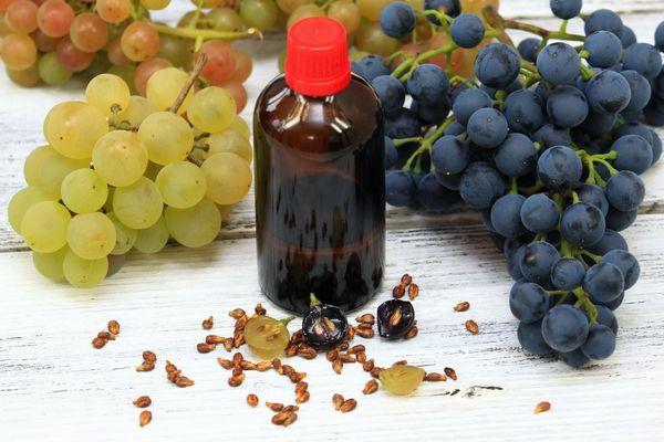 Egy asztalon fehér és kék szőlő, előttük szőlőmagok és üvegcsében szőlőmagkivonat.