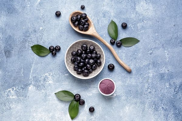 Egy szürkés kék asztalon egy tálban, egy fakanálban és mellette acai bogyók, egy kis tálban őrölt acai bogyó.