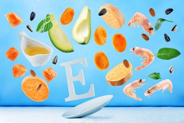 Egy kék háttér előtt fehér E betű, körülötte E-vitamint tartalmazó élelmiszerek, rákok, avokádó, napraforgómagok, spenótlevelek, sárgarépa szeletek, sütőtök darabok, olívaolaj.