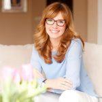 Középkorú vörös hajú hölgy otthon a kanapéján ül és mosolyog.