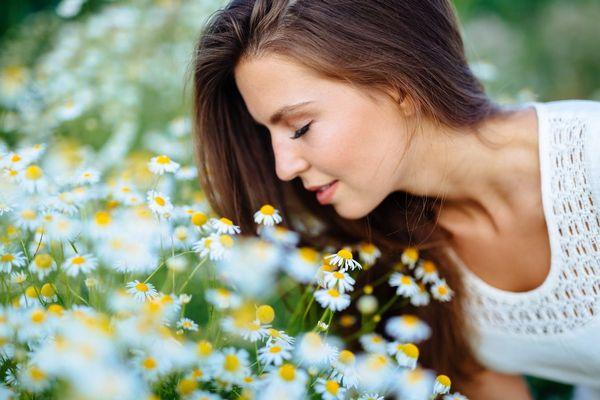 Fiatal nő kamillamezőn kamillavirágokat szagol.