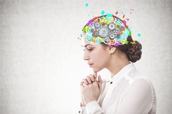 Egy szürke háttér előtt fiatal nő két kezét összetéve tartja a fejét, fejére imitált agy montírozva.