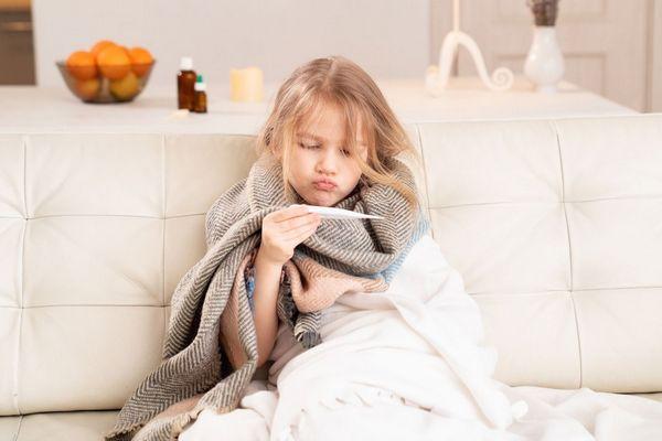 Egy nappali kanapéján egy beteg kislány takaróba betakarva ül, a kezében levő hőmérőt nézi.