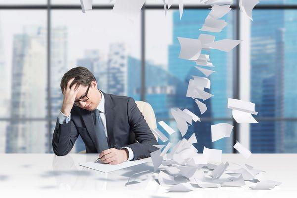 Egy irodában egy fáradt öltönyös férfi fejét tartja a kezével, próbál dolgozni, papírra írni, mellette papírok repülnek.