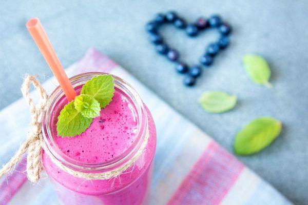 Egy asztalon egy üvegben áfonyából készült smoothie, mellette áfonyaszemek szív formában kirakva.