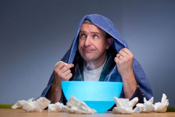 Egy náthás férfi kék törölközővel a fején inhalál, körülötte sok elhasznált papír zsebkendő.