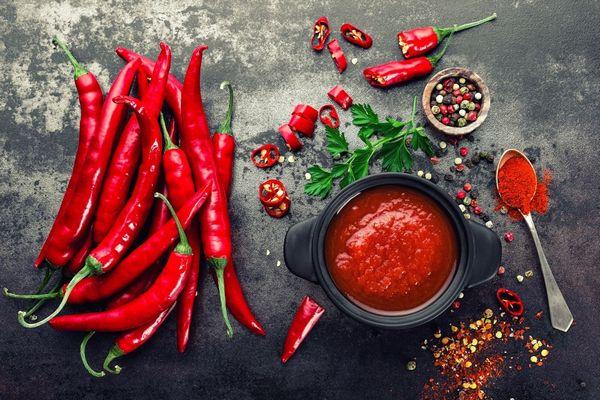 Egy szürke asztalon izzadást fokozó egész és szeletelt chili paprikák, egy kanálban és mellette őrölt chili, és egy szürke tálban chiliszósz.
