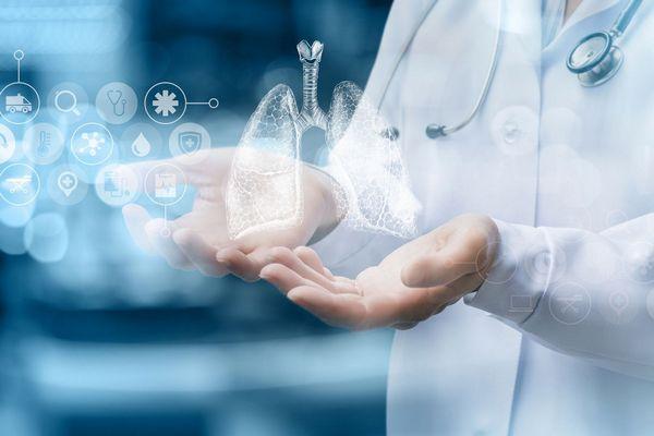 Egy fehér köpenyes orvos két kezét kinyújtja, melyek felett egy imitált tüdő látható.