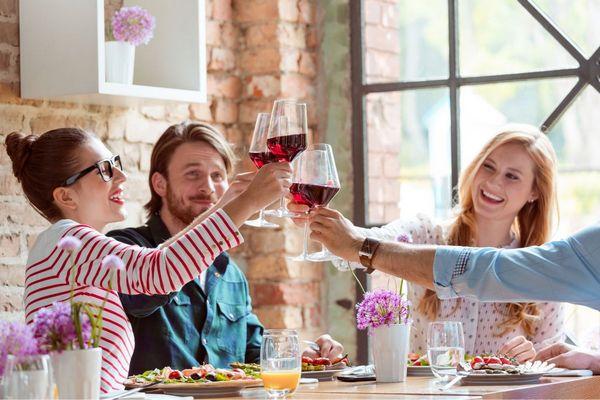 Egy mosolygós baráti társaság ebédel, kezükben vörösboros poharat tartanak, miközben koccintanak.