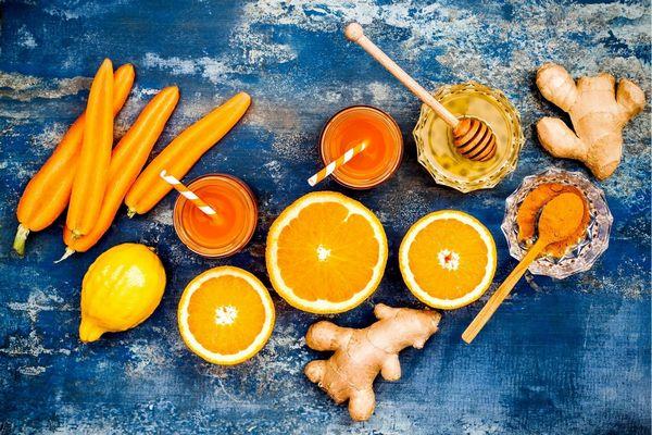 Egy kék asztalon sárgarépák, gyömbér, narancsok, citrom, pohárban sárgarépalé, mellette üvegtálban méz.