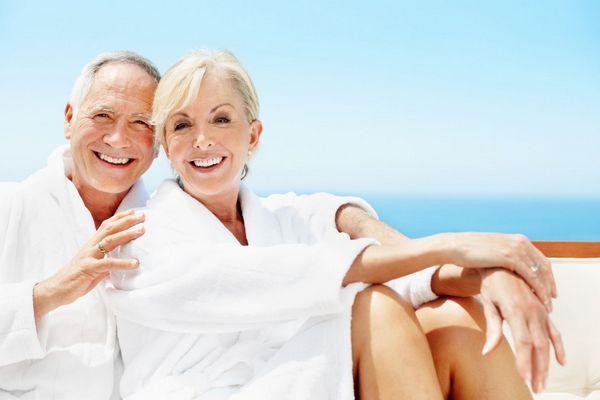 Tengerparton fehér ruhában egy nyugdíjas házaspár ül és mosolyog.