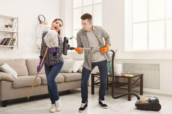 Egy fiatal pár az otthonában viccelődve takarít, a lány a felmosó moppot mikrofonként tartja, a fiú a porszívó csövével gitározik.
