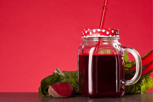 Egy piros háttér előtt egy üvegben céklalé, mellette céklaszelet és céklalevelek.