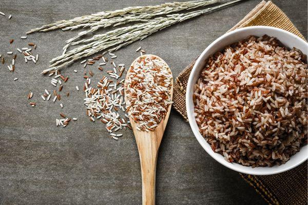 Egy asztalon egy tálban és egy fakanálban barna rizs, mellette kalászok.