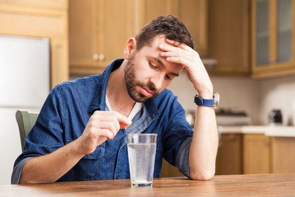 Egy férfi a konyhájában fájós fejét tartja a kezével, gyomorégés miatt egy pohár vizet készül inni.