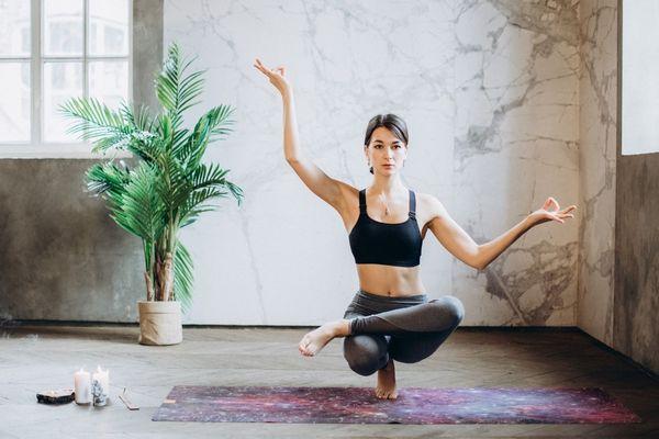 Egy szobában egy fiatal nő kitekert pozícióban jógázik.
