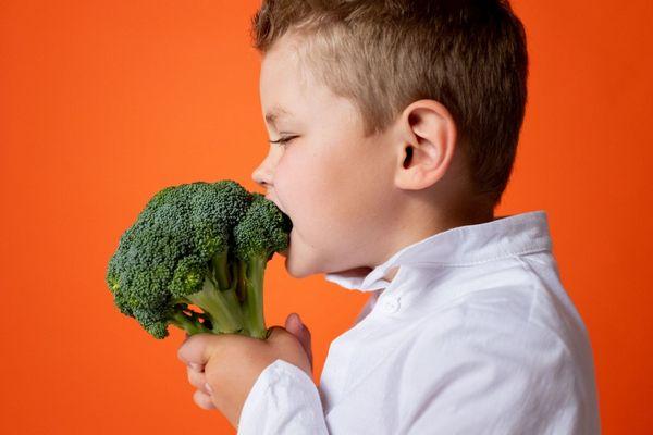 Egy narancssárga háttér előtt egy kisfiú brokkoliba harap.