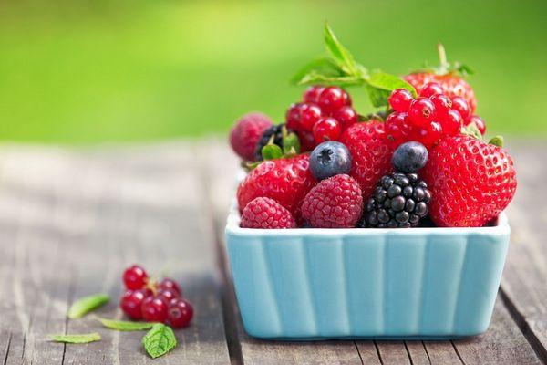 Egy asztalon kék tálban és mellette bogyós gyümölcsök, piros ribizli, szeder, málna, eper, fekete áfonya.