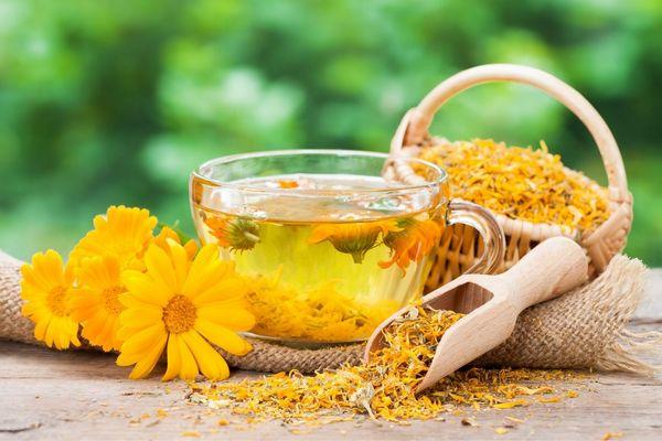 Egy asztalon üveg csészében körömvirágtea, mellette körömvirágok és szárított körömvirágok kosárkában és fakanálban.